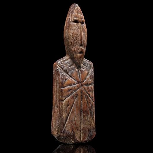 A miniature tattooed shaman figure representing a spiritual ancestor